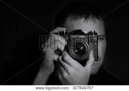 Close-up Black And White Portrait Of A Photographer With An Old Slr Camera In His Hands On A Dark Ba