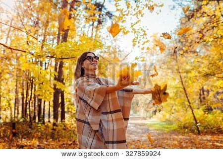 Fall Season. Woman Throwing Leaves In Autumn Forest. Young Woman Having Fun Outdoors