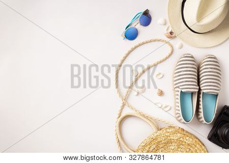 Flat lay traveler accessories on white background with straw hat, summer shoes, camera, bag and sunglasses.