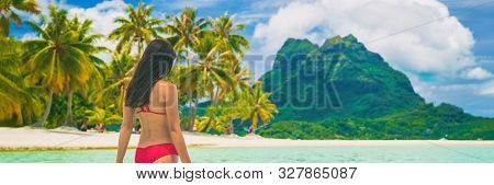 Tahiti luxury travel beach in Bora Bora cruise destination. Idyllic paradise banner background woman in bikini relaxing walking in sun.