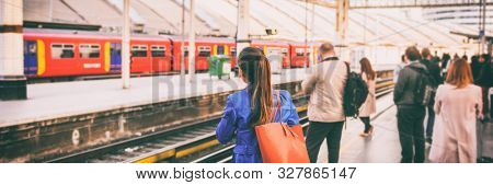 Commuters going to work waiting at train station platform in London city, UK, Europe banner panorama. Train public transport commuting network woman passenger with orange purse panoramic banner.