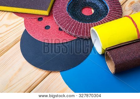 Set of abrasive tools different colors and sandpaper on wooden background poster