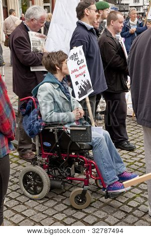 A Protester In A Wheel-chair Holds A Anti-cuts Placard  At Exeter Cathedral Yard As Part Of The May