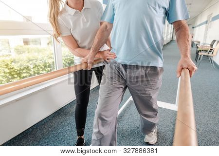 Senior Patient and physical therapist in rehabilitation walking exercises, she is helping him along the bars