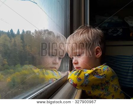 A Little Blond-haired Boy Of Three Years Rides On A Train, Eats Candy And Looks Out The Window, Behi
