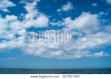 White Fluffy Clouds, Like Blond-haired Horses, Fly Across The Sky Above A Blue Strip Of The Sea.