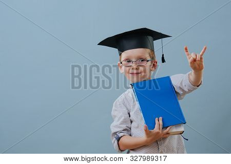 Redhead First Grader Boy In Glasses And Student Hat Making Rock-n-roll Gesture
