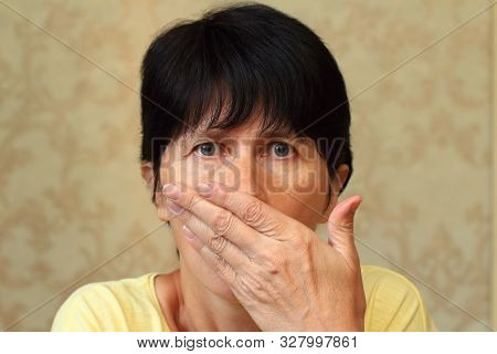 Middle Aged Woman. The Emotions Of Fright, Fear, Panic. She Covered Her Mouth With Her Hand
