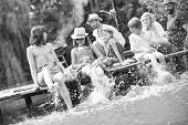 Black and white photo of mother playing water with kids in lake while sitting on pier against family at lakeshore during summer poster