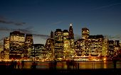 image of the new york city skyline at night. taken at the brookly piers poster