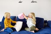 Pillow fight. Mischievous preschooler children jumping on a sofa and hitting each other with pillows. Boy and girl play together. Active games for siblings at home. poster