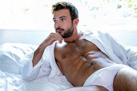 Sexy Hairy Man With Beard, Blue Eyes, Lying In Bed In Underwear And Open Shirt Revealing Sixpack Abs