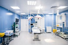 Interior of surgery room in modern clinics with all necessary equipment along walls and surgical table in center with lamps above