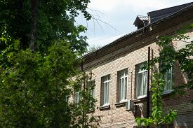 Old Brick Building With White Windows And Vegetation Near It