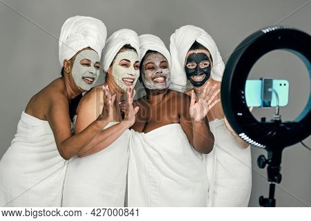 Happy Multiracial Females Having Skin Care Spa Day While Streaming On Social Network With Mobile Sma