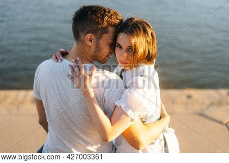 Close-up Back View Of Beautiful Young Happy Couple In Love Hugging, Sitting On Bench On City Waterfr