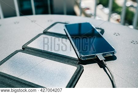 Charging A Smartphone From Home With A Portable Solar Panel Charger.self-consumption And Charging Wi