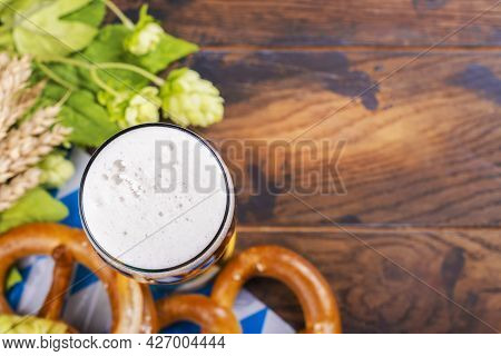 Glass Of Beer And Traditional Oktoberfest Food - Salted Pretzels On Wooden Background. Copy Space