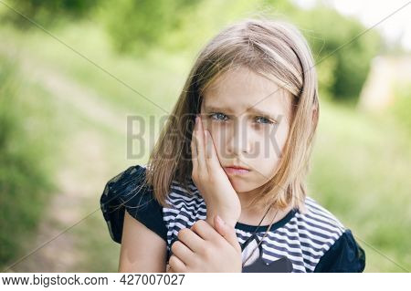 The Young Girl Suffers From Toothache And Is Very Angry With Pain. She Went To Walk In The Park And
