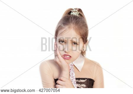 A Beautiful Young Girl With Light Hair Sad On A White Background Holds Her Cheek And Suffers From To