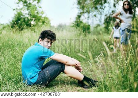 A Teen With Dark Hair Sitting On The Grass Embracing His Legs And Angry. Mother Is Behind Him. A Tee
