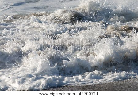 Close up of foamy ocean waves on a sunny day