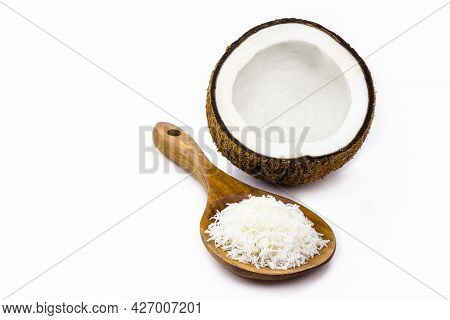 Wooden Spoon With Grated Coconut And Coconut In The Background, Isolated On White Background With Co