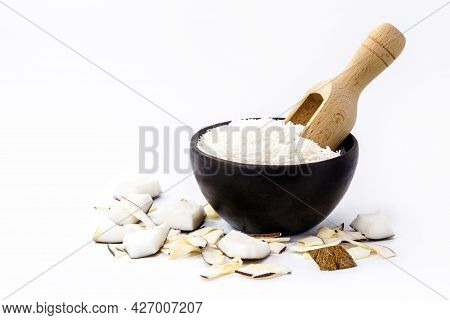 Handmade Earthenware Bowl With Grated Coconut And Wooden Measuring Spoon, Isolated White Background