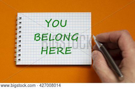 You Belong Here Symbol. Businessman Writing Words You Belong Here On White Note. Beautiful Orange Ba