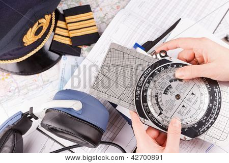 Close up of an airplane pilot hand holding flight computer and making pre-flight calculations with equipment including hat, epaulettes and other documents in background
