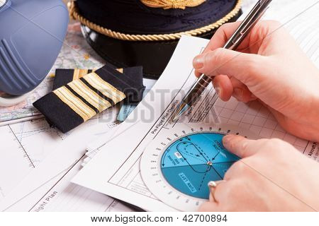 Close up of an airplane pilot hand filling in an flight plan with equipment including hat, epaulettes and other documents in background poster
