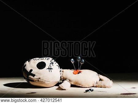 Pins With Skulls Stabbed In A Voodoo Doll For Your Magic Ritual On A Black Background