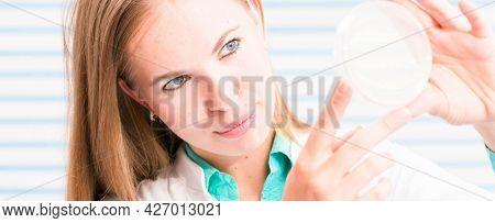 A nurse in the hospital's laboratory analyzes petri dishes