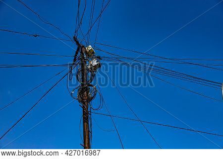 Street Pole With Many Electrical Wires And Fiber Optic Cables, Fiber-optic Cable Against The Blue Sk