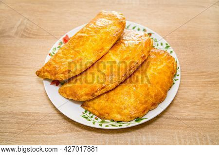 Baked Puff Pastry With Delicious Yellow Cheese On A Round Plate On A Wooden Board Background. Bakery