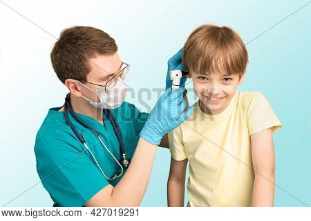 Pediatric Pediatrician Man Examines The Ears Of The Child With An Otoscope In The Clinic. The Boy Sm
