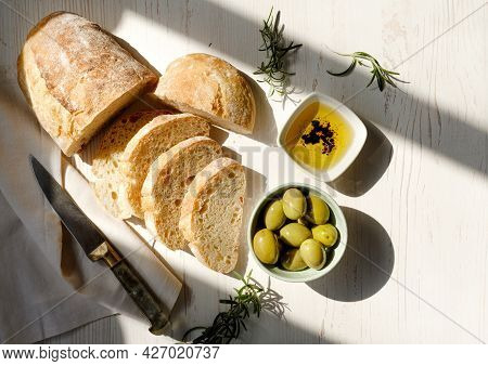 Sliced Organic Bread Ciabatta With Vintage Linen Napkin And Bowl Of Olive Oil, Olives, Rosemary On W