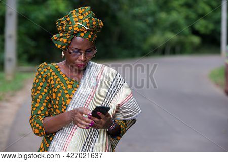 Young African Woman Standing In Loincloth And Glasses Looking At Mobile Phone.
