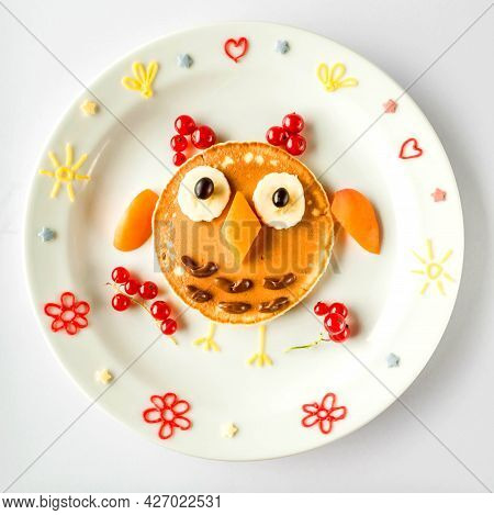 Edible Owl Made Of Pancake With Apricot And Currant For Kids. Plate With Funny Pancake. Funny Breakf