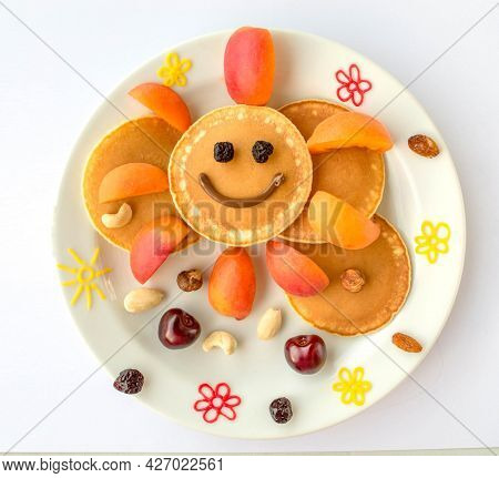 Edible Sun Made Of Pancake With Apricot And Dried Fruits, Nuts For Kids. Plate With Funny Pancake. F