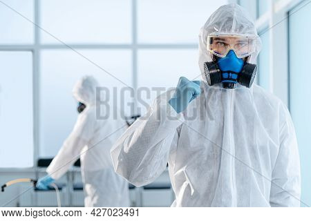 Confident Young Disinfector Standing In An Infected Room .