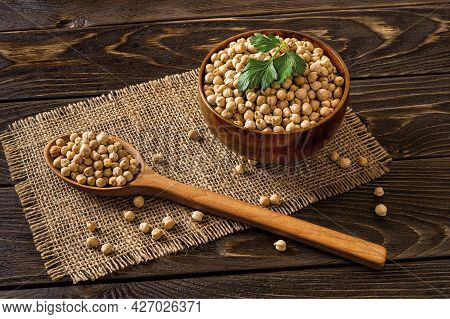 Wooden Bowl And Large Spoon Both Full Of Raw Chickpea Beans Over Black Rustic Table. Low Key Image O