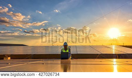 Engineer Using Laptop At Solar Panels On Rooftop At Sunset Sky, An Engineer Working At A Photovoltai
