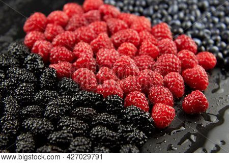 Mix Of Fresh Raspberries, Blueberries And Mulberries Laid Out In A Row, Berry Background.