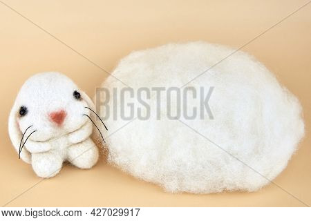 Handmade Felted Bunny Near A Piece Of Wool On A Beige Background.