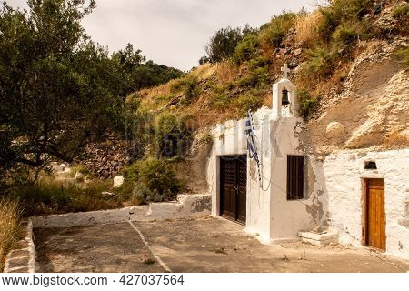 Old Whitewashed Small Christian Church Built In A Rock On A Hill On Milos Island Near Trypiti Town W