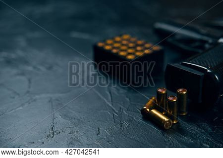 Close-up Of Gun Handle And Bullets On Concrete Table. Firearms And Ammunition. Concept Of Defense Or