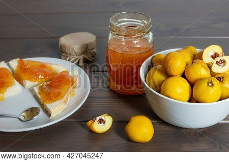 Homemade Quince Jam On A Wooden Background. Jar Of Jam, Toast And Quince Fruit In A Bowl On The Tabl