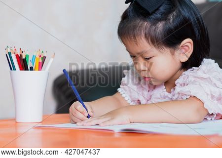 Portrait Of Asian Pupil Girl Doing Homework At Home. Child Holding Color Pencil With Right-hand. Kid