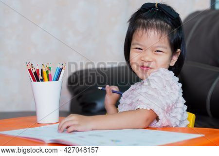 Pupil Girl Sweet Smiling, Looking At The Camera. Happy Student Learning At Home. Home School. Baby A